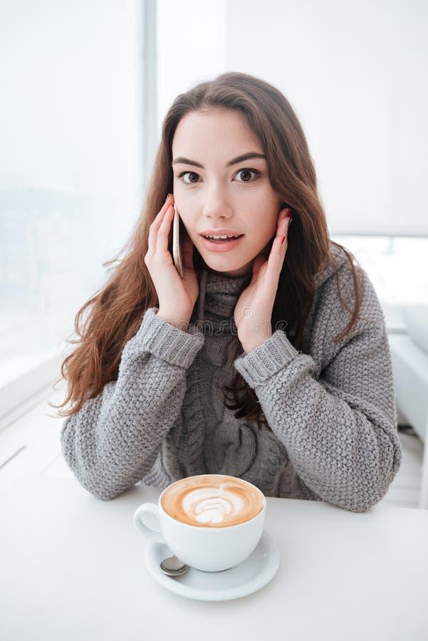 迷茫的小姐饮用的咖啡,当谈话由电话时 免版税图库摄影