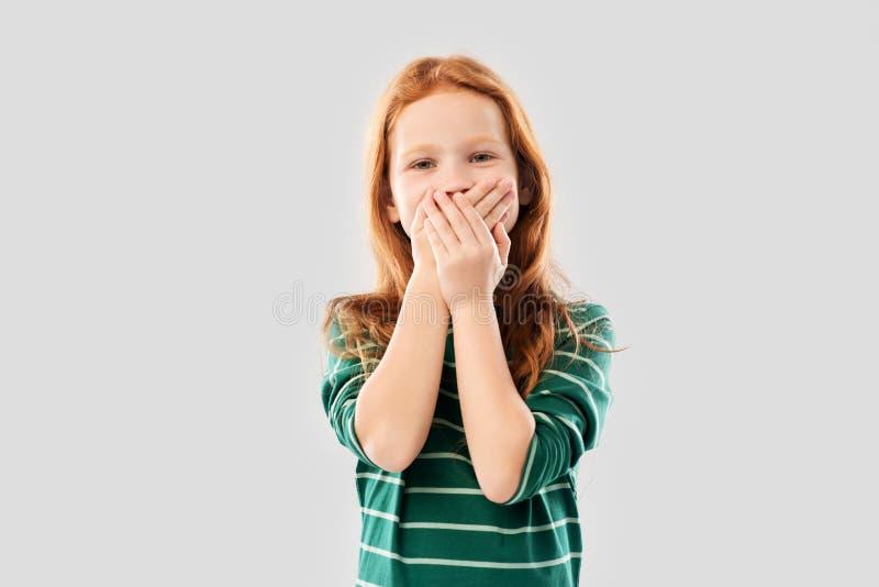 迷茫的红发女孩覆盖物嘴用人工 免版税图库摄影
