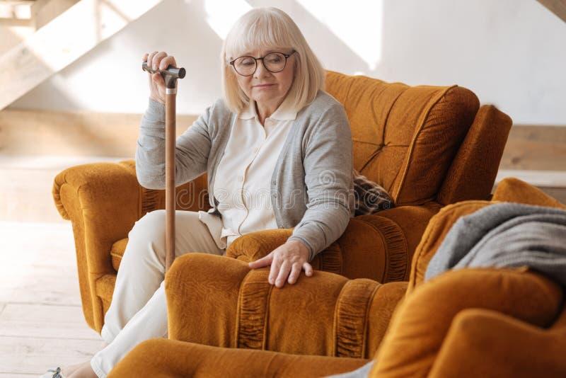追悼关于她的丈夫的沮丧的年迈的妇女 免版税库存图片