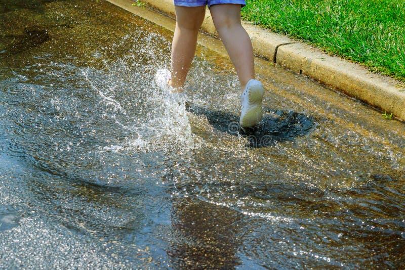 追捕和跳跃在水坑的儿童女孩雨在夏天 图库摄影