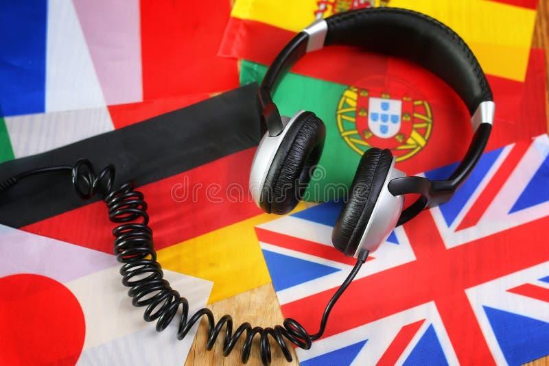 追猎语言耳机和旗子在桌上 免版税图库摄影