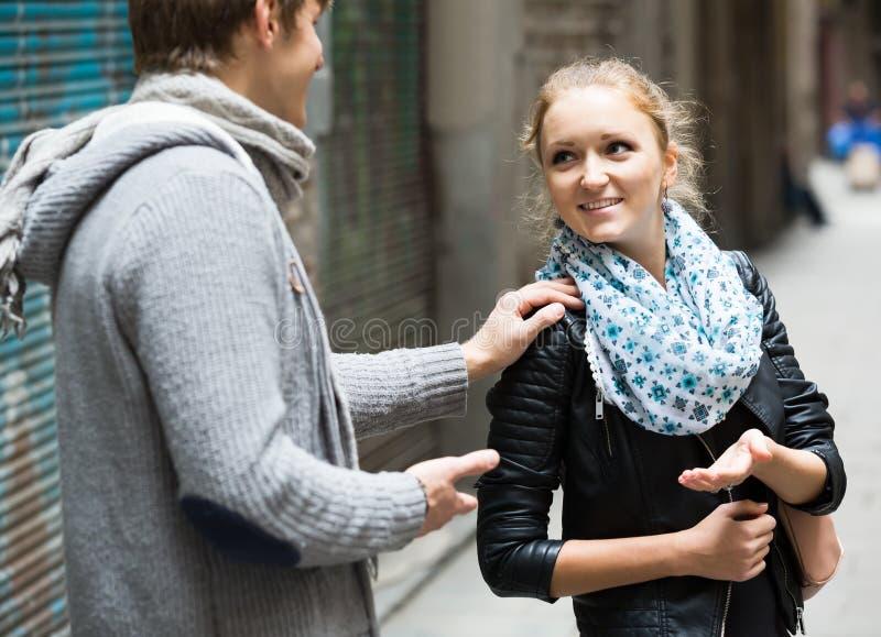 追逐喜悦的女孩的好男学生在室外日期 免版税图库摄影