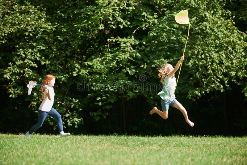 追逐在夏天领域的两个女孩蝴蝶 免版税库存图片