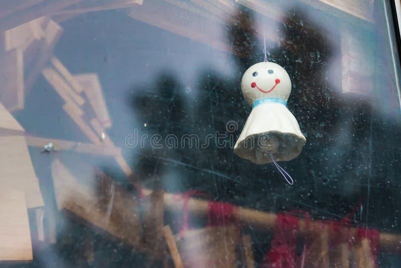 追逐垂悬在窗口里的雨日本玩偶 库存图片