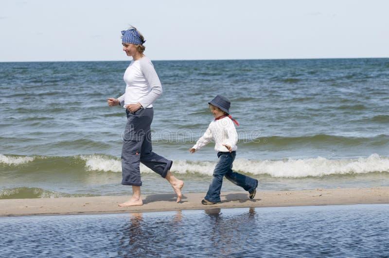 追逐女儿母亲的海滩 库存照片
