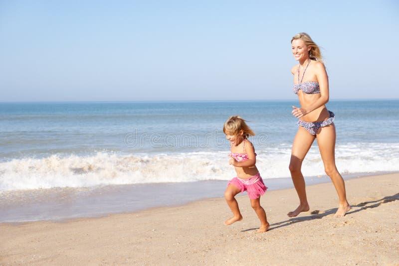 追逐女孩母亲年轻人的海滩 免版税库存图片