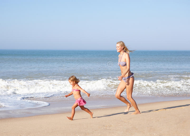 追逐女孩母亲年轻人的海滩 图库摄影