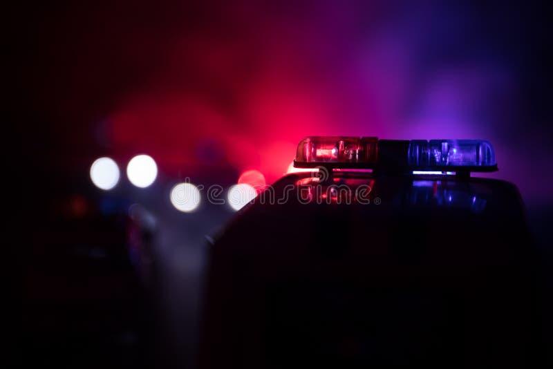 追逐汽车的警车在晚上有雾背景 加速对罪行场面的911应急警车  有选择性的foc 免版税库存照片