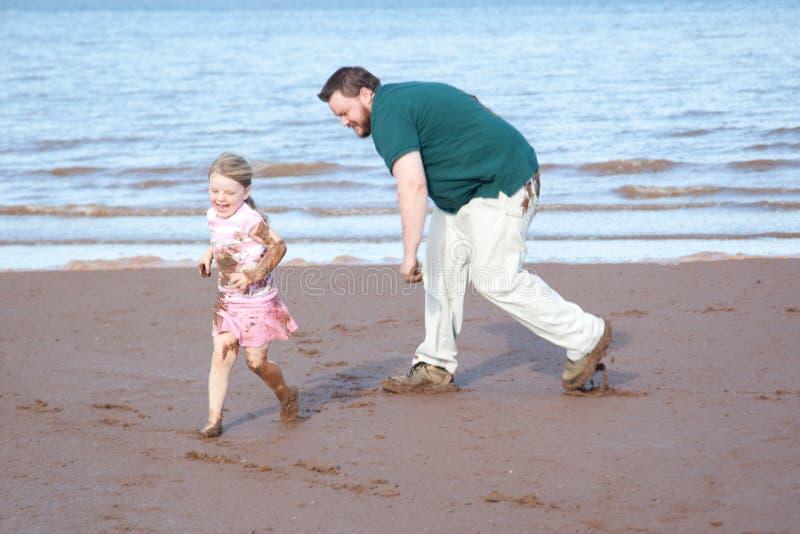 追逐泥泞的海滩的父亲女儿 免版税库存图片