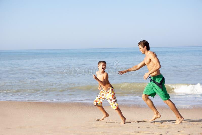 追逐父亲年轻人的海滩男孩 库存图片