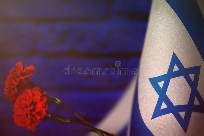 退伍军人日或阵亡将士纪念日荣誉的以色列旗子与两朵红色康乃馨花 对战争概念o的以色列英雄的荣耀 免版税库存照片
