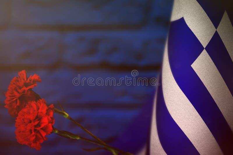 退伍军人日或阵亡将士纪念日荣誉的希腊旗子与两朵红色康乃馨花 对战争概念的希腊英雄的荣耀 免版税库存照片