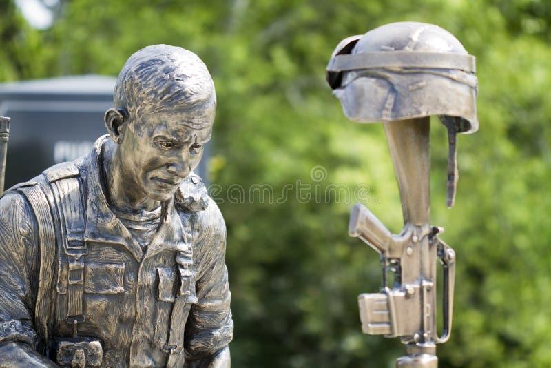 退伍军人纪念战士盔甲和步枪古铜色雕象 免版税库存图片