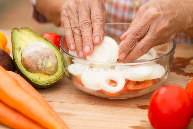退休与由她的自已庭院在家增长的菜和果子的资深妇女厨师沙拉 库存照片