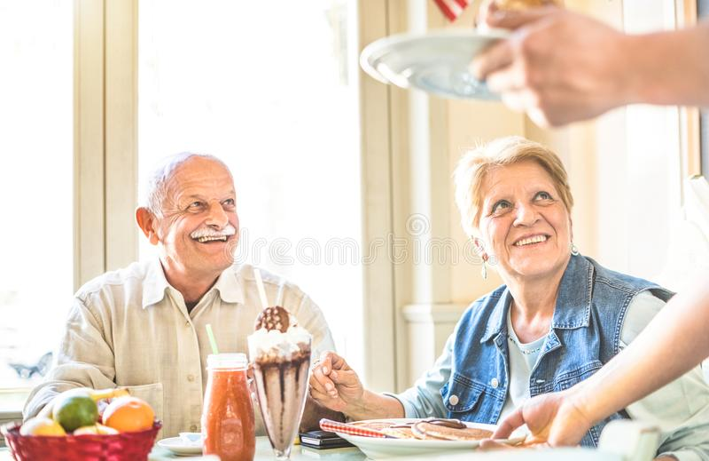 退休了夫妇吃蛋糕的侍者服务的前辈在时尚酒吧 库存图片