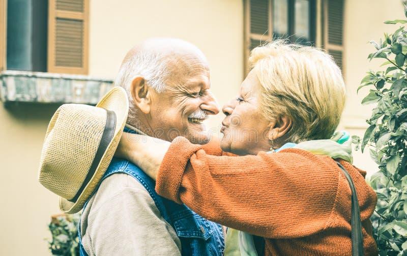 退休了夫妇获得乐趣亲吻户外在旅行时间的愉快的前辈 图库摄影