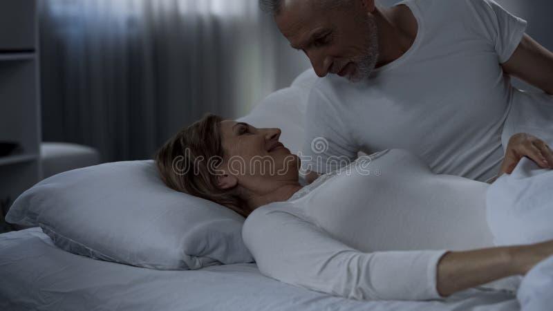 退休人员男性和女性在床上和微笑,愉快地已婚,柔软 免版税图库摄影