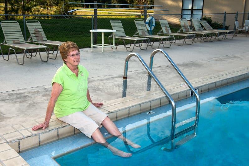退休公共资深妇女由游泳池放松 免版税库存图片