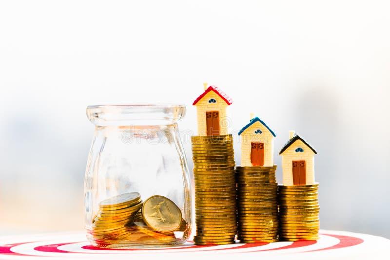 在硬币堆的议院模型 买一个家庭概念的硬币计划的储款金钱  免版税库存图片