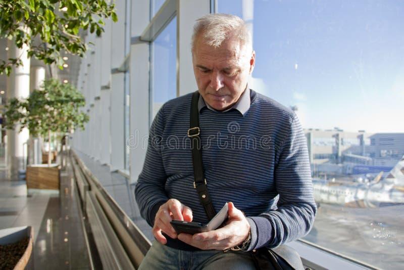 退休年龄的一个人在机场 图库摄影