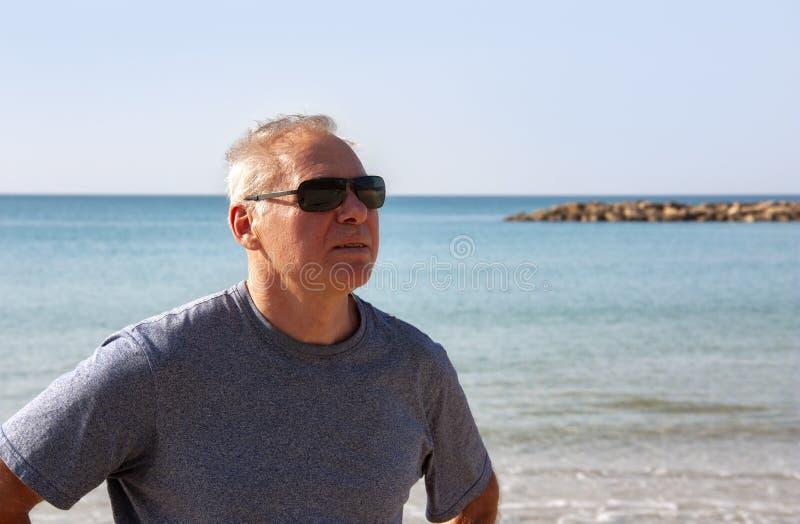 退休年龄的一个人的画象在海的背景的 免版税库存图片