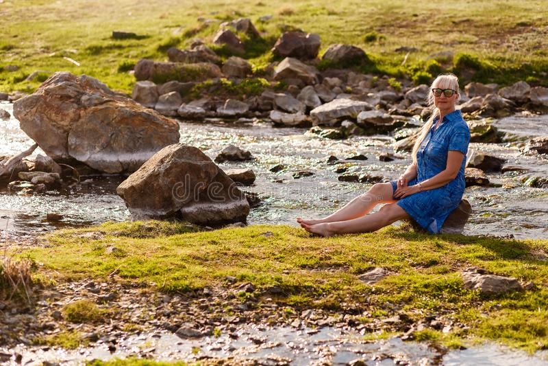 退休年龄的微笑的美女在一件蓝色礼服的坐石头靠近河在日落 免版税库存图片