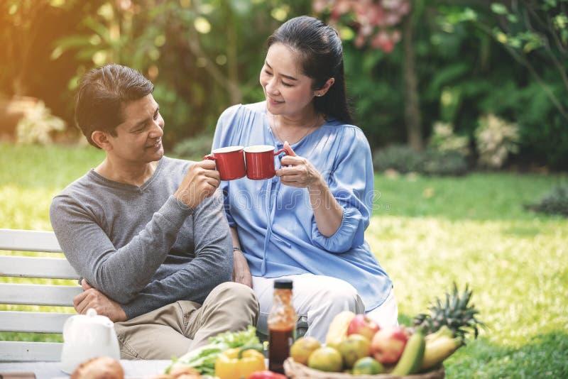 退休更老的恋人有一起dringking咖啡用新鲜的水果和蔬菜的时间作为前景在后院 图库摄影