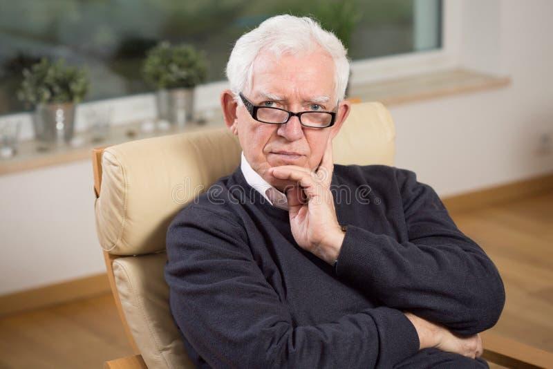 退休的人坐椅子 免版税库存照片