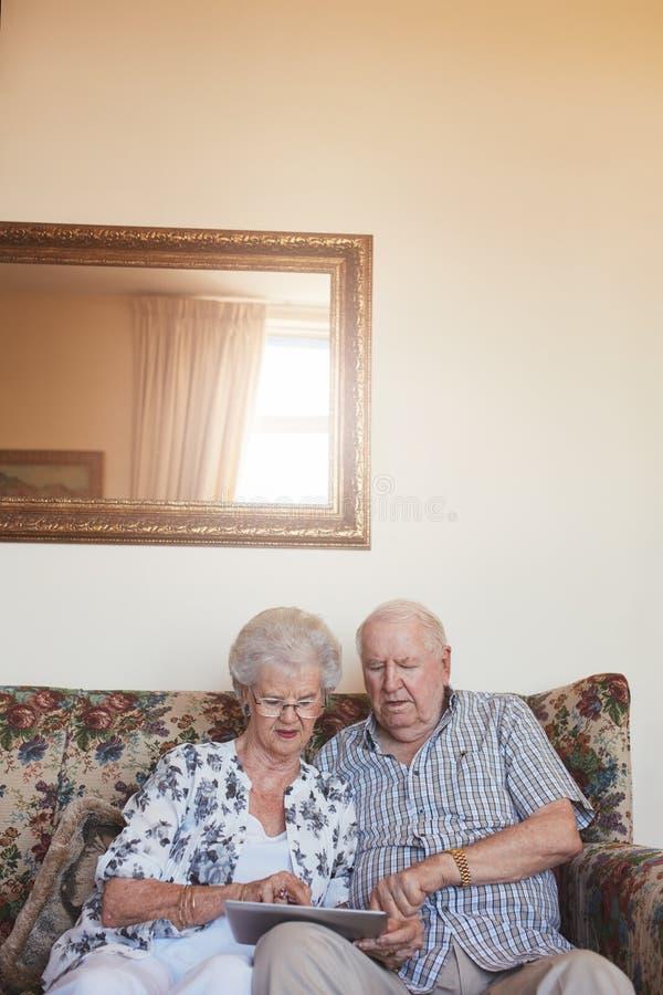 退休的夫妇在家使用数字式片剂 库存照片