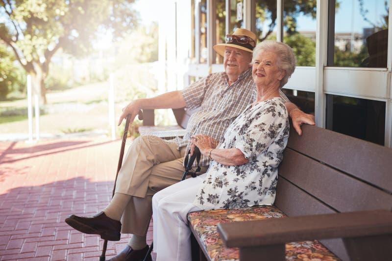 退休的夫妇坐一条长凳他们的家外 免版税图库摄影