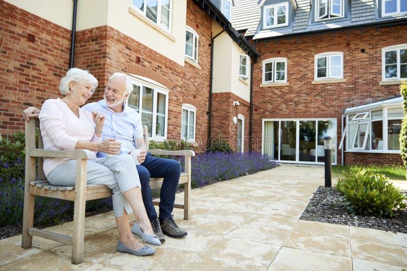 退休的夫妇坐与热的饮料的长凳在协助的生存设施 库存图片