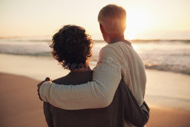 退休的夫妇观看的惊人的日落 库存图片