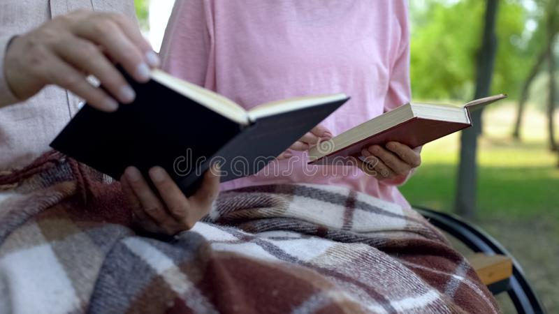 退休的夫妇阅读书,开会公园长椅一起,退休金业余时间 图库摄影