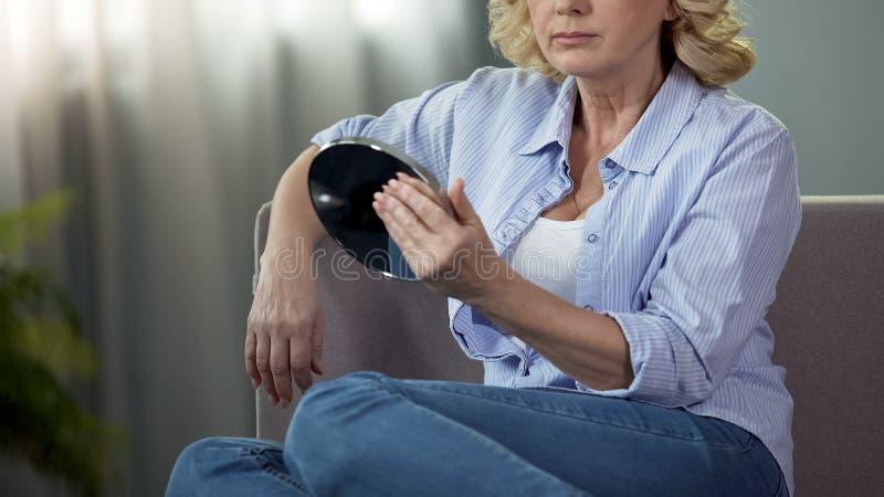 退休的女性看起来的手中镜子,在家坐长沙发,整容 图库摄影