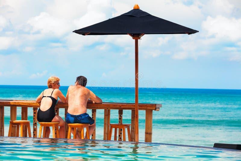 退休的成熟夫妇松弛海滩游泳池 免版税库存照片