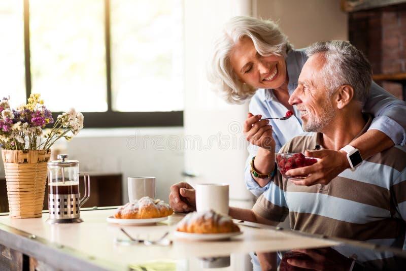 退休的男人和妇女食用早餐在厨房 免版税库存照片