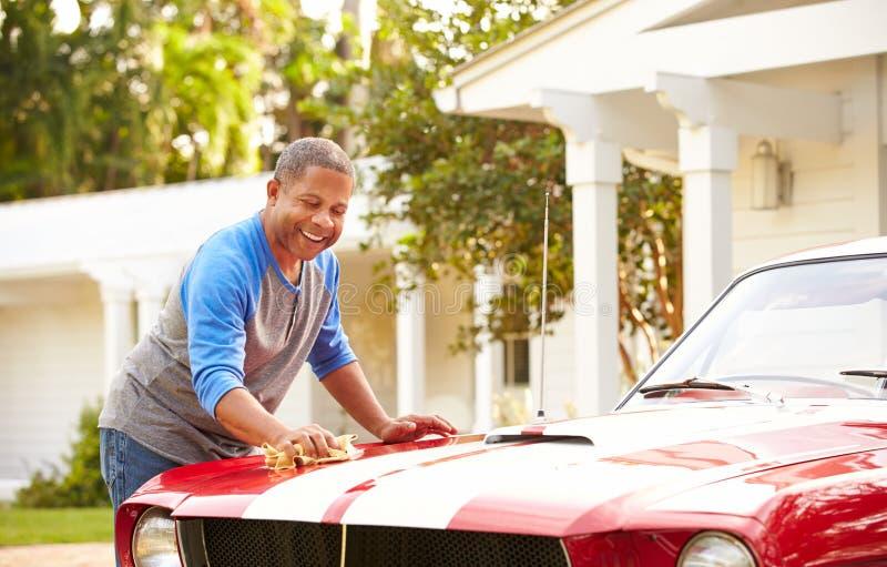 退休的老人清洁被恢复的汽车 免版税库存照片
