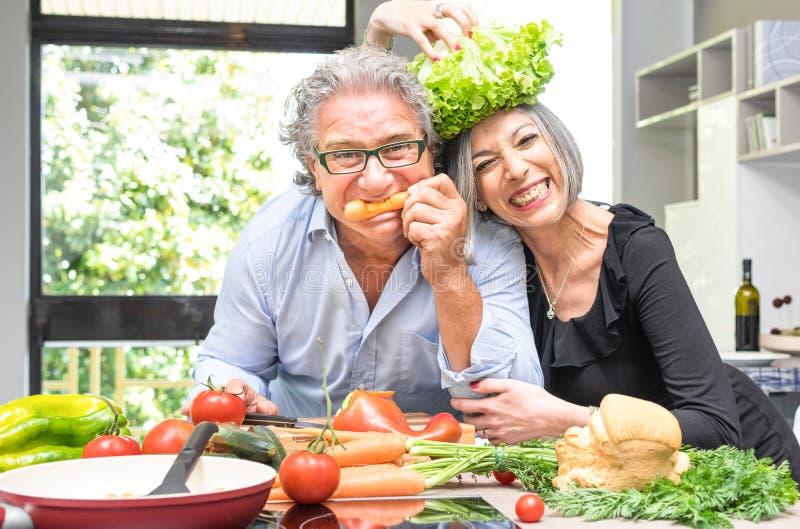 退休的资深夫妇获得乐趣在厨房用健康食物 图库摄影