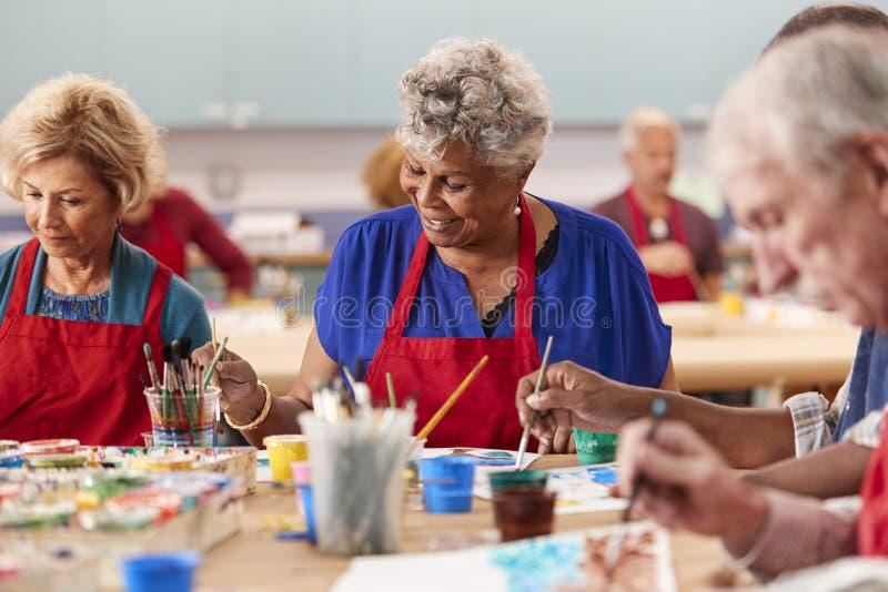 退休的资深妇女在社区活动中心的上艺术课 库存照片