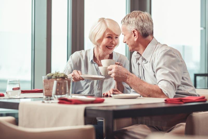 退休的食用男人和的妇女早晨咖啡一起 免版税库存照片