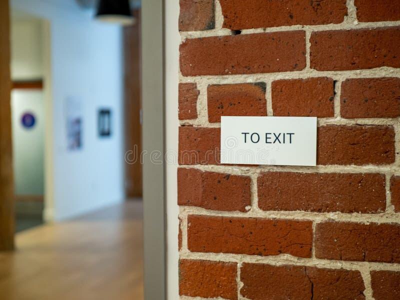 退出在砖墙上的标志在一个现代仓库大厅办公室区域 免版税库存图片