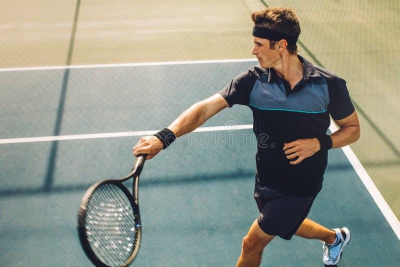 退回与强有力的正手击球的网球员服务 免版税库存照片