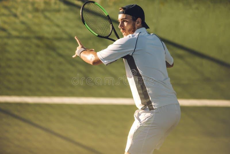 退回与正手击球的网球员服务 图库摄影