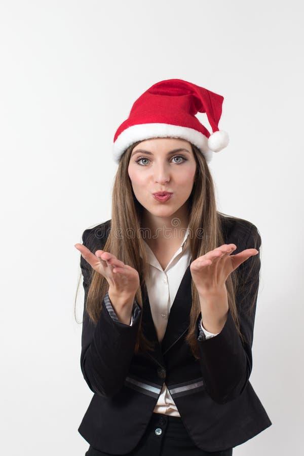 送与圣诞老人红色圣诞节帽子的年轻女商人一个飞吻 免版税库存照片