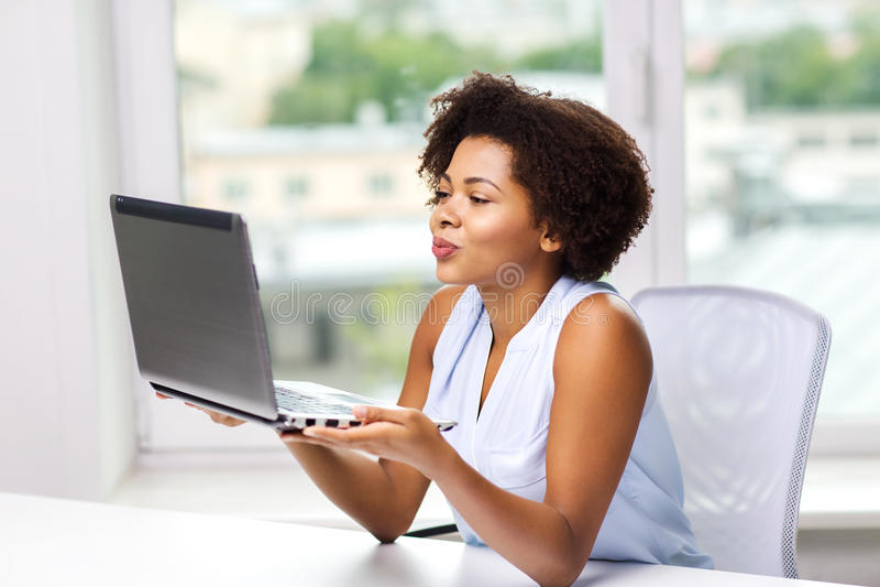送亲吻的非洲妇女到便携式计算机 库存照片