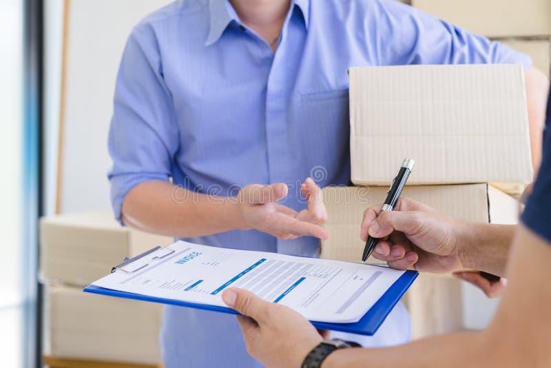 送命令的年轻男性起始的小企业主包装到顾客和标志在发货票票据 免版税库存图片