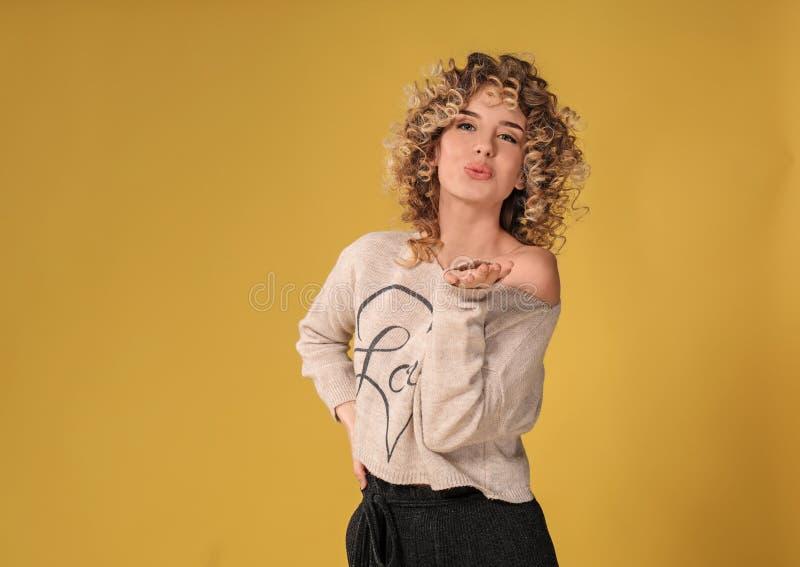 送在颜色背景的美丽的年轻女人画象手亲吻 免版税库存图片