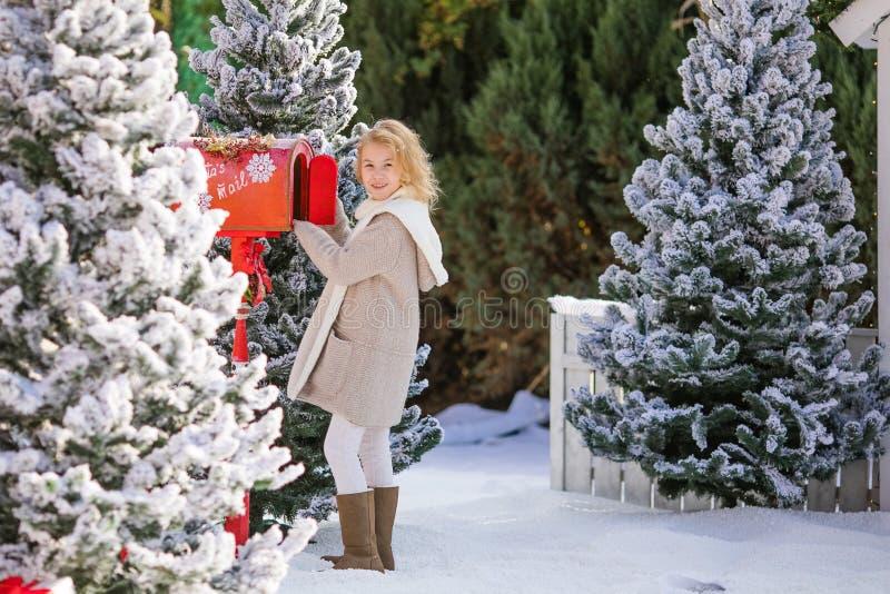 送她的信到圣诞老人,圣诞节时间的可爱的白肤金发的女孩 免版税库存照片