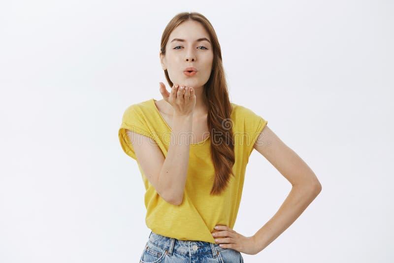送我热情的亲吻 迷人的美丽的白种人女性画象有红色头发的在黄色T恤杉折叠的嘴唇 库存图片