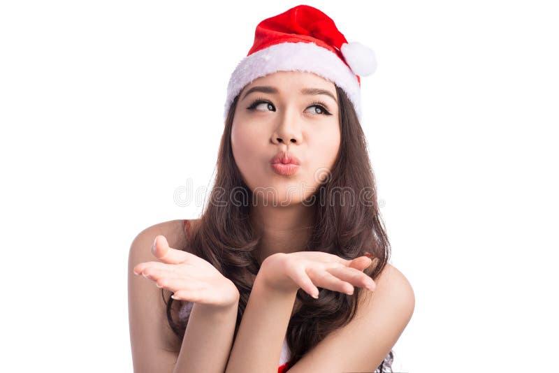 送打击k的圣诞老人帽子和红色礼服的美丽的亚裔妇女 免版税库存图片